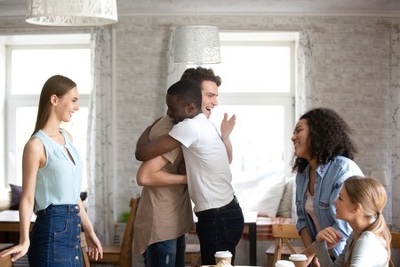 Diverse students gathered together during lunch. Guys buddies best friends hugging greeting each other at meeting in cafe surrounded by attractive multi-ethnic girls. Friendship and reunion concept Standard-Bild