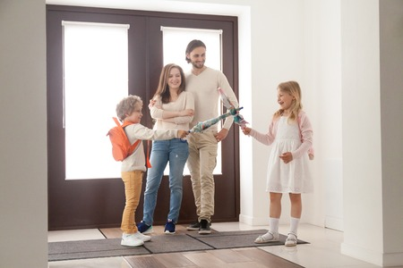 Funny family standing in hallway and gather to school or for a walk at home. Husband and wife embracing and looking at their playful children. Daughter and son play like a duel or sword with umbrellas