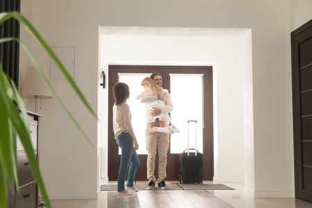 Married couple, little preschool daughter standing in hallway at home. Sincere father hug girl with love tender, she missed him. Male arrived with suitcase luggage from business trip. Reunion concept