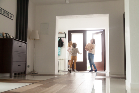Three person in hallway near entrance door at home. Happy little preschool daughter and son meet their mother after shopping, buying provision in grocery market, holding paper bags full of fresh food Reklamní fotografie