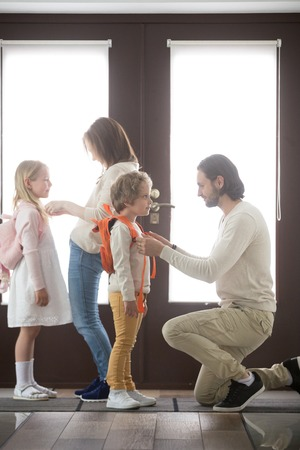 Young married couple and little children standing in hallway at home. Parents helps to preschool daughter and son gather to school or for a walk. Happy family weekend, free time and parenting concept Stock Photo