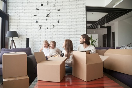 Happy family together in living room. Parents sitting on couch and unpacking cardboard boxes, little playful daughter and son playing. Buy real estate, relocating at new house and mortgage concept 免版税图像