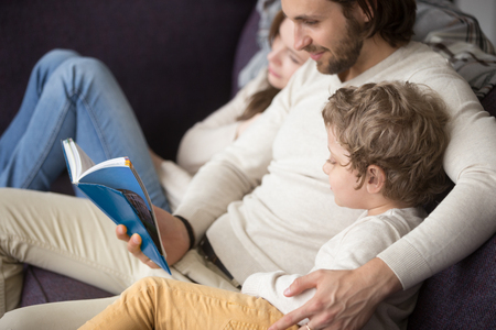 Young family sits on couch in living room at home. Loving husband read a fairytale book wife and little preschool son listen with interest. Concept of education, development of thinking, imagination