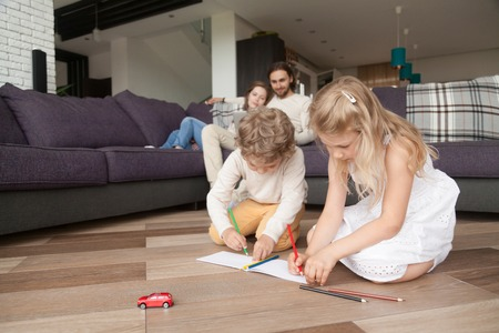 Married relaxed couple with preschool children in living room. Parents sitting on couch using computer, little daughter and son on warm wooden floor drawing. Happy family together at new home concept