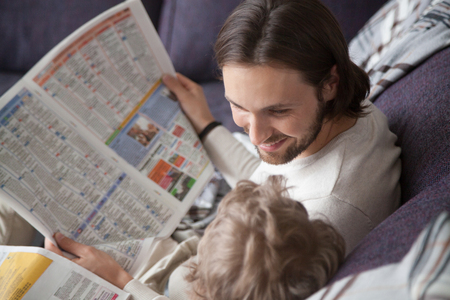 Close up family spending free time weekend at home. Father looking with love tenderness and laughing with little intelligent smart son reading news newspapers sitting together on couch in living room