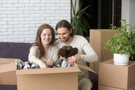 Happy young married couple sitting together on couch in living room at new house. Smiling wife and husband unpacking personal stuff. New home, tenant, moving and relocation, loan and mortgage concept