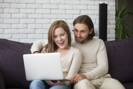 Surprised happy couple sitting together on couch in living room at home or hotel room. Excited husband and wife using computer, buying via internet online, booking tickets and great discount concept