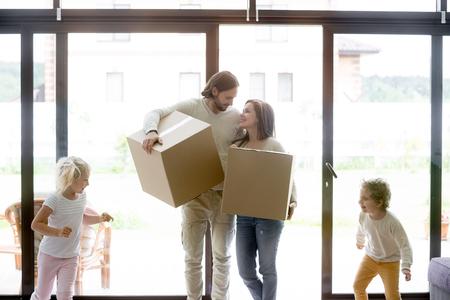Verheiratetes junges Paar betritt Wohnzimmer mit kleinen Kindern. Familie, die in neues Haus umzieht. Lächelnde Eltern, die ungeöffnete Pappkartons halten, fröhlicher Kleinkindsohn und -tochter, die herumlaufen und herumspielen