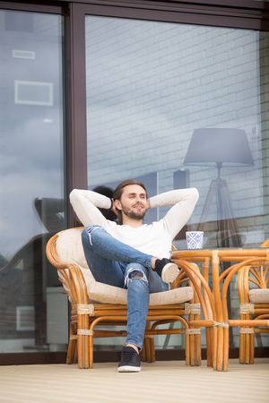 Positive young millennial man sitting on outdoors armchair putting his hands behind head, breathing resting and enjoying fresh spring air opposite of new modern house. Leisure good day successful male
