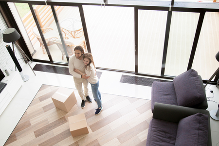 Young happy married couple embracing standing in living room, unopened cardboard boxes with belongings on floor. Smiling wife and husband buying new real estate. Moving, relocation or mortgage concept