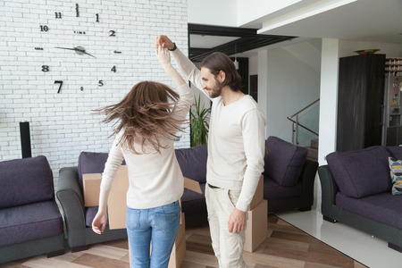 Married excited young couple dancing in sitting room at home. Happy husband and wife celebrating their relocation at new house, purchasing real estate. Belongings still is at unopened cardboard boxes