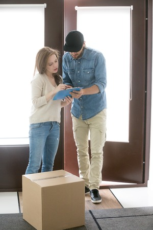Female and male standing in hallway at home. Positive courier brings a cardboard box package to customer client woman. Surface mail, buying and order goods by post service by online internet concept Stock Photo