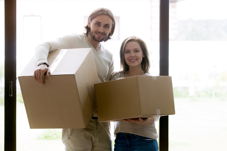 Young smiling married couple standing with unopened cardboard boxes with their belongings and looking at camera. Positive wife and husband in new house. Moving, buying real estate or mortgage concept