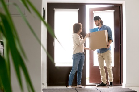 Female and male standing in hallway at home. Positive courier bring a cardboard box package to customer client woman. Surface mail, buying and ordering goods by post service by online internet concept