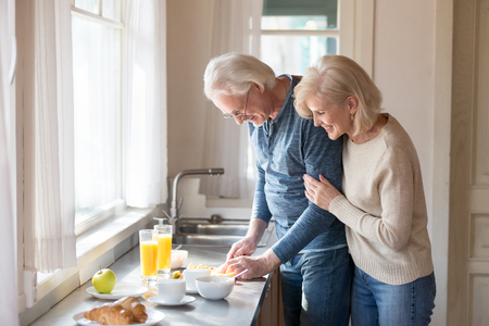 Smiling aged wife hug man from behind watching him preparing healthy food, loving senior woman embrace husband cooking breakfast slicing fruit, romantic couple spend morning at home together Banco de Imagens
