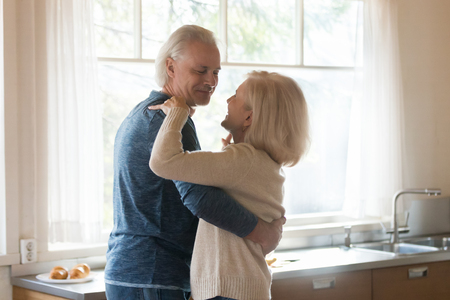 Smiling aged couple in love dancing in kitchen distracted from food preparing, happy senior husband and wife move swirling spending morning at home, romantic elderly man and woman sway or waltz