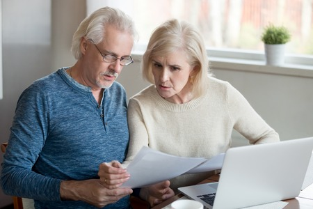 Ernstige oude man en vrouw beheren energierekeningen met behulp van laptop thuis, bezorgd senior paar lezen banklening of hypotheekdocumenten aan keukentafel, oudere man en vrouw controleren verzekeringspapier