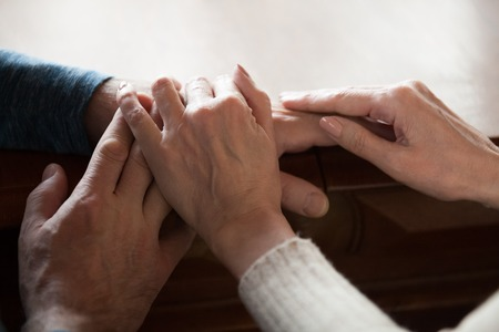 Close up of caring aged wife caressing husband hands showing love and support, romantic senior couple touching comforting each other, elderly man and woman enjoying tender moment at home together Stok Fotoğraf