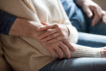 Close up of romantic aged couple relax on couch at home cuddling spending time together, sensual senior husband hug wife touching and caressing, tender elderly spouses embrace enjoying romance