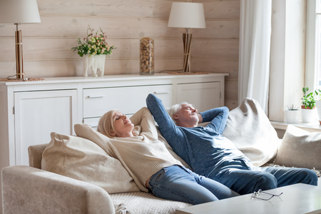 Peaceful elderly couple sleep on cozy couch spending weekend in countryside, calm senior husband and wife relax on sofa dreaming with eyes closed, aged man and woman take a nap resting at home