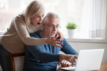 Shocked senior husband and wife pointing at laptop screen seeing unbelievable information, surprised aged couple notice unexpected on computer, elderly man and woman amazed by online news Archivio Fotografico