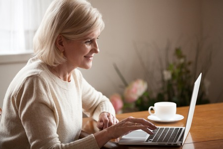 Excited aged woman using laptop, browsing internet at home, smart senior lady working at computer drinking coffee indoors, busy elderly female surfing web, checking mail or reading news online