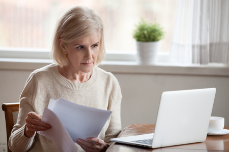 Serious aged woman holding documents, checking information at laptop online, concerned senior female managing bank insurance or loan papers, busy working at computer. Elderly and technology concept Standard-Bild