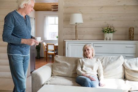 Un mari âgé attentionné fait du thé pour sa femme bien-aimée qui passe le week-end à la campagne, un homme âgé aimant apporte une boisson chaude à une femme souriante âgée qui se détend à la maison ensemble. Concept de mariage réussi