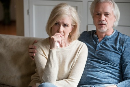 Emotional senior husband and wife watch sad movie relaxing on cozy sofa at home, sensitive aged couple spend weekend together enjoying drama series or soap opera, elderly female nervous for film plot