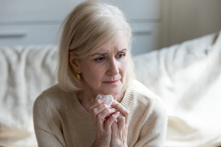 Sad aged lady crying sitting on couch lost in thoughts and memories of past god life, sorrowful senior woman grieve for passed away husband missing him, upset elderly female feel lonely and abandoned Stockfoto