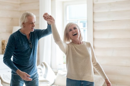 Happy senior husband and wife have fun spending time in country house together, smiling aged couple dance swirling and swaying at home, excited elderly man and woman waltz turning around