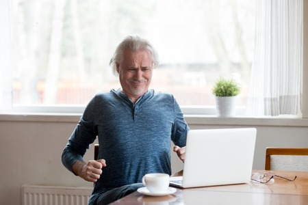 Exhausted aged man suffering from back pain sitting too long in incorrect posture, tired senior male stretch in chair working at laptop having body spasm or strain. Sedentary lifestyle problem concept