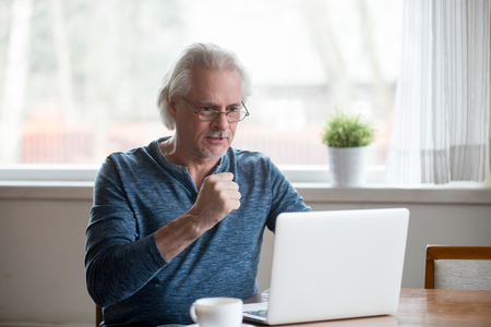 Excited senior man using laptop happy winning online lottery, satisfied aged male watching sports game or match on computer celebrating victory, elderly glad reading good news working at pc at home
