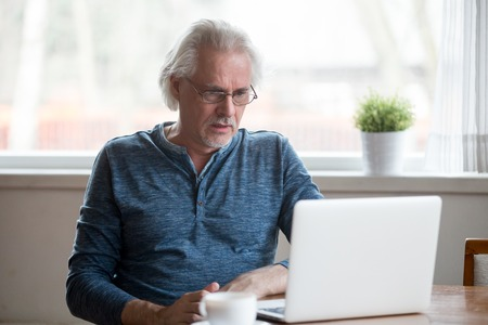 Confused senior male use laptop looking at screen shocked by received message or letter, stunned aged man frustrated by unexpected bad news online, disappointed elderly get negative response in email