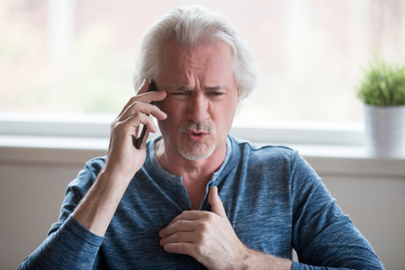Angry aged man talk over cellphone arguing or having dispute with another person, determined senior male prove point of view involved in phone discussion, using smartphone speaking with someone Stock fotó