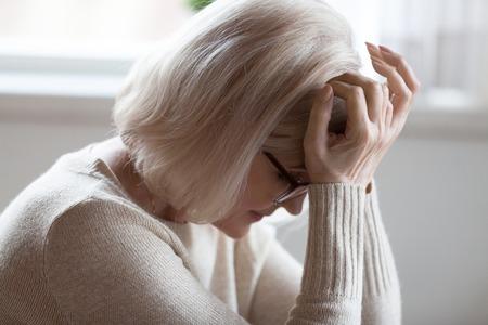 Vermoeide oudere vrouw lijdt aan ernstige hoofdpijn zittend met gesloten ogen, uitgeputte oudere vrouw voelt zich onwel met sterke pijn of duizeligheid, overstuur bejaarde dame in wanhoop slecht hartverscheurend nieuws krijgend Stockfoto