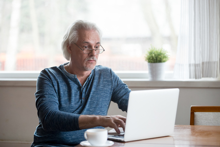Surprised aged man stunned getting error or mistake message working at laptop, senior male using pc shocked by unexpected computer problem or virus attack, elderly amazed reading news online