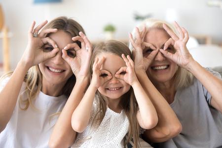 Fröhliche Kinderenkelin, Mutter und Großmutter, die ein lustiges Porträt haben, fröhliche 3 Generationen Frauenfamilie, die lächelt und lustige Gesichter mit Blick auf die Kamera macht, Oma, Mutter und Kind, die zusammen das Gesicht verziehen Standard-Bild