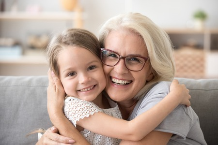 Happy old grandmother hugging little grandchild girl looking at camera, smiling mature mother or senior grandma granny laughing embracing adopted kid granddaughter sitting on couch, headshot portrait Stockfoto - 112482649
