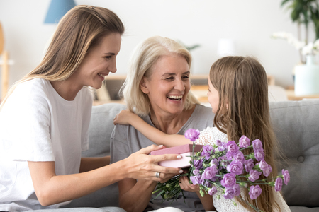 Happy grandma embracing little granddaughter thanking grandchild and grown daughter for gift box holding flower bouquet, smiling child girl and mother congratulate granny with birthday giving present