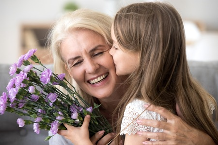 Little preschool granddaughter kissing happy older grandma on cheek giving violet flowers bouquet congratulating smiling senior grandmother with birthday, celebrating mothers day or 8 march concept Banco de Imagens