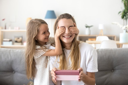 Little cute daughter closing eyes of excited mommy holding gift box sitting on couch, cute preschool child girl making surprise for happy mom, present for mothers day or birthday from kid concept 스톡 콘텐츠
