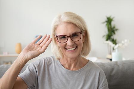 Sonriente mujer de mediana edad agitando la mano mirando a la cámara, anciana madura con gafas haciendo video blog o llamada en casa, vlogger senior amigable feliz sentado en el sofá citas en línea, retrato de tiro en la cabeza Foto de archivo