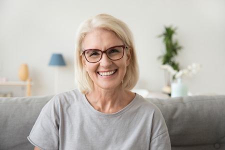 Lächelnde reife grauhaarige Frau mittleren Alters, die in die Kamera schaut, glückliche alte Dame mit Brille, die zu Hause drinnen posiert, positive alleinstehende Seniorin im Ruhestand, die auf dem Sofa im Wohnzimmerkopfschussporträt sitzt sitting