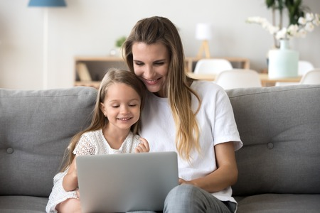 Smiling mother and kid daughter having fun shopping online sitting on sofa, happy mom baby sitter teaching little child girl use laptop application, watching cartoon or making video call on computer Stock Photo