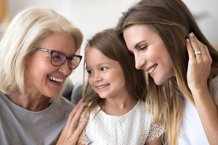 Smiling loving three generation of women concept laughing, grandmother, daughter and child girl bonding together, happy senior old grandma embracing kid granddaughter and grown mom having fun at home