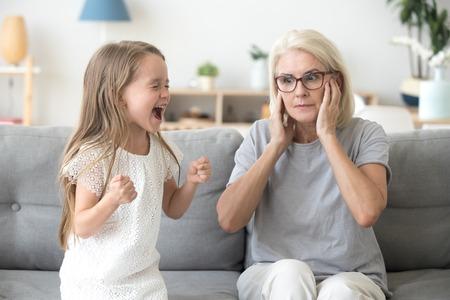 Abuela sorprendida cerrando los oídos para no escuchar a la nieta ruidosa obstinada y quisquillosa gritando exigiendo atención, niña de niño mimado preescolar gritándole a la abuela, concepto de manipulación de rabieta infantil