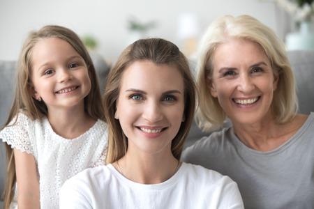Jeune femme adulte souriante regardant la caméra avec une vieille mère et une petite fille, une mère millénaire posant avec une fille et une grand-mère, une famille heureuse de trois générations ensemble, portrait