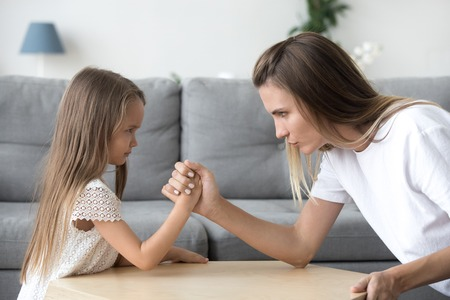 Mom and kid daughter arm wrestling having fight confrontation or family conflict, mother in law and stubborn child girl holding hands competing with serious focused faces expressing disagreement