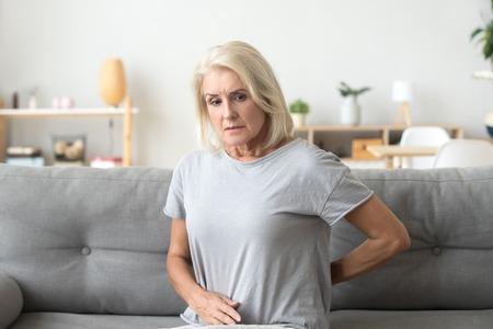 Besorgte traurige reife ältere Frau, die den Rücken berührt und verspannte Muskeln massiert, verärgerte ältere Frau, die an chronischen Schmerzen im unteren Lendenwirbelbereich leidet, Rückenschmerzen Arthritis Osteoarthritis Radikulitis Konzept